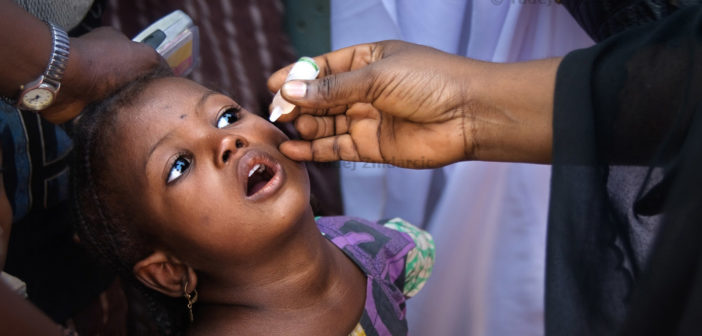 Girl receives polio vaccine in Kaduna, northern Nigeria city, during polio national immunization days (NIDs). NIDs are held four times a year and teams of vaccinators try to reach every child in Nigeria. Despite their efforts many parents still don't immunize their children.