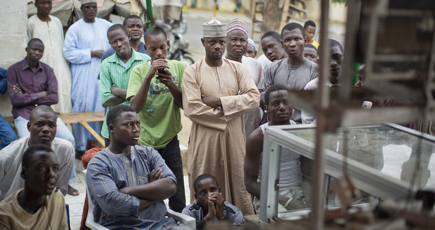 Nigerian men watch as the election commission announces electoral results for certain states, on a television at an outdoor butchery in Kano, northern Nigeria Tuesday, March 31, 2015. The second day of vote counting in Nigeria's bitterly contested presidential vote started late on Tuesday and electoral officials hope to announce later in the day who will govern Africa's richest and biggest nation. (AP Photo/Ben Curtis)