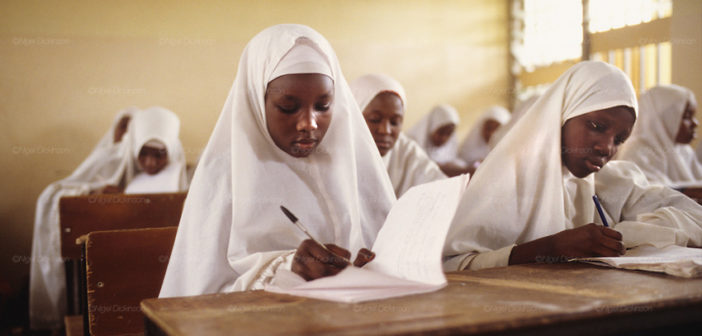 Islamic school for girls and young women in Kano  The implementation of Islamic Sharia Law across the twelve northern states of Nigeria, centres upon Kano, the largest Muslim Husa city, under the feudal, political and economic rule of the Emir of Kano. Islamic Sharia Law is enforced by official state apparatus including military and police, Islamic schools and education, plus various volunteer Militia groups supported financially and politically by the Emir and other business and political bodies. Fanatical Islamic Sharia religious traditions  are enforced by the Hispah Sharia police. Deliquancy is controlled by the Vigilantes volunteer Militia. Activities such as Animist Pagan Voodoo ceremonies, playing music, drinking and gambling, normally outlawed under Sharia law exist as many parts of the rural and urban areas are controlled by local Mafia, ghetto gangs and rural hunters. The fight for control is never ending between the Emir, government forces, the Mafia and independent militias and gangs. This is fueled by rising petrol costs, and that 70% of the population live below the poverty line. Kano, Kano State, Northern Nigeria, Africa