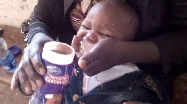 A mother-force-feeding-her-baby